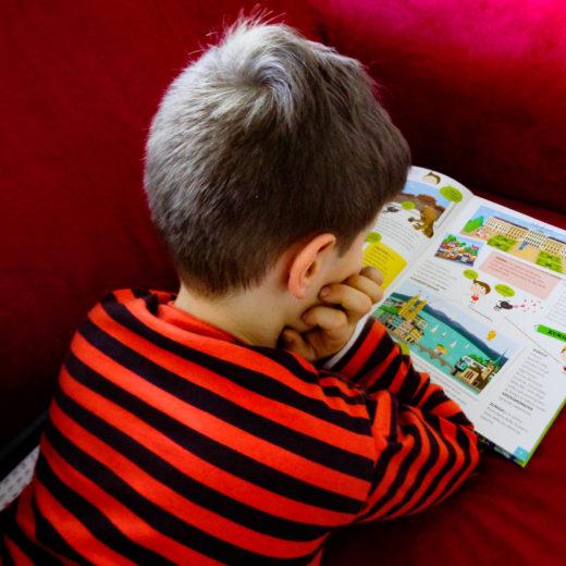 bambino che legge libro di viaggio
